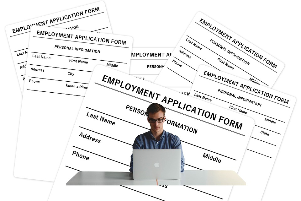 Pic of job seeker on laptop with paper applications behind him