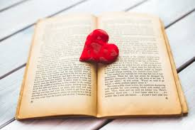 Open book with red heart on top.