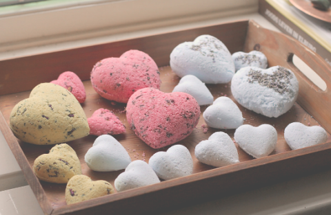 Heart shaped bath bombs sitting in a wooden tray.