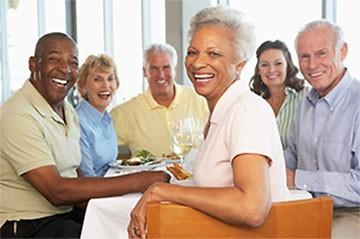 Group of senior sitting at a table smiling