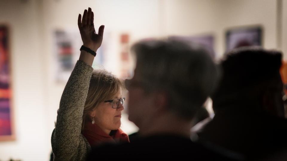 Woman raising hand to answer question